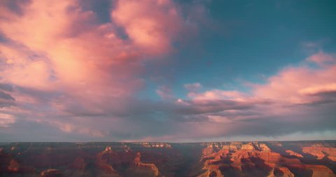 Amazing shot Grand Canyon vista at sunset with beautiful lighting, clouds, red cliffs and blue skies in 4K DCI.