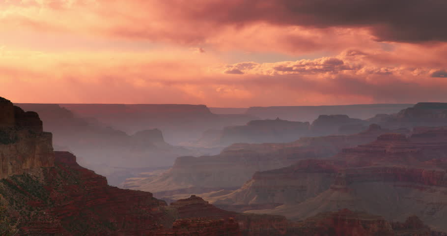 Dramatic shot of Grand Canyon at sunset with amazing lighting, clouds, red cliffs and blue skies in 4K DCI. | Shutterstock HD Video #1019904940