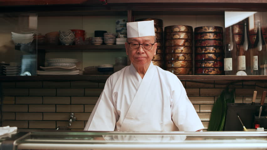 Portrait of experienced serious sushi chef standing behind a counter in his small traditional sushi bar with soft interior lighting. Medium shot on 4k RED camera. | Shutterstock HD Video #1019910580