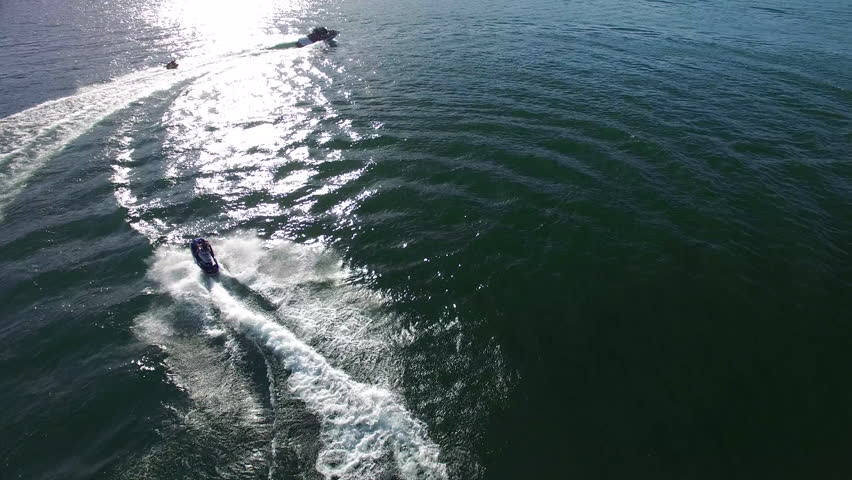 A personal watercraft follows a boat pulling a tube on a perfect summer's day out on the lake. | Shutterstock HD Video #1019926360