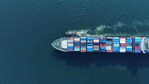 Aerial top view of cargo container ship and trug ship working dragging vessel to yard port concept freight shipping ship.