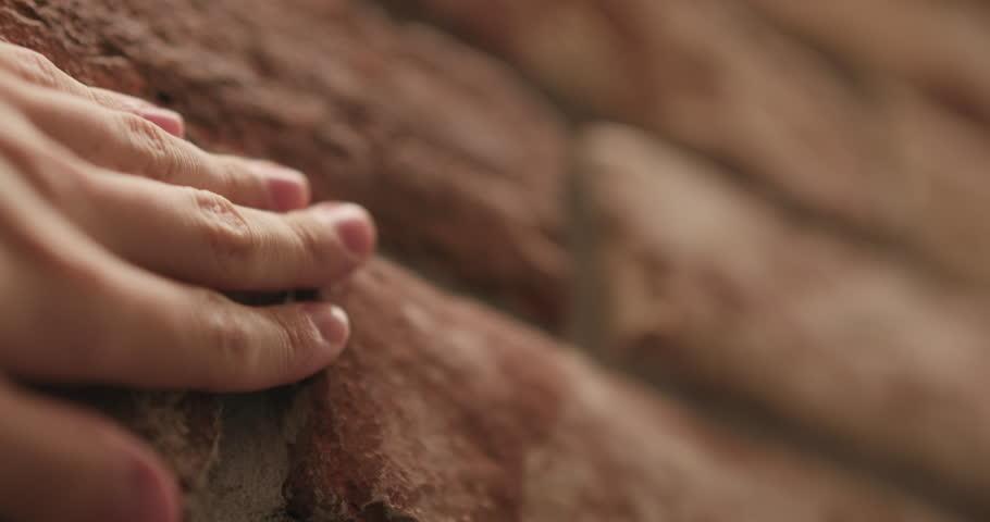 Slow motion closeup man hand touching old brick wall handheld shot #1019963530