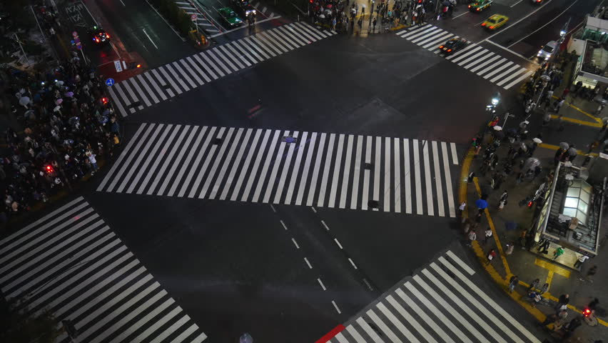 Tokyo Japan 10 Nov 2018 : Aerial time lapse view over Shibuya crossing with many pedestrians and vehicles crossing the junction in Tokyo Japan at night time. Shibuya is fashion shopping entertainment.