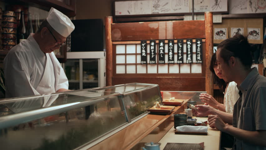 Content Japanese couple eating sushi and talking with the chef in small sushi bar with soft interior lighting. Medium close up shot on 4k RED camera. | Shutterstock HD Video #1020021250