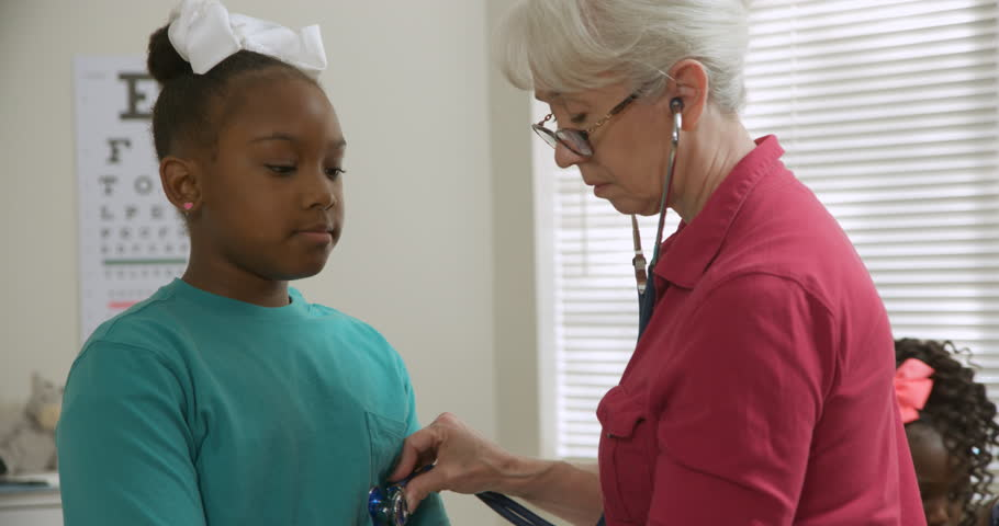 Focus in scene moves from a mature Caucasian pediatrician listening to heart beats of a cute African American girl to her mother and sister who sit waiting for examination results. | Shutterstock HD Video #1020030730