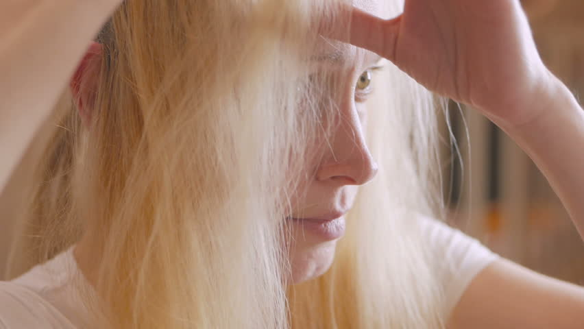 A woman brightens her hair roots at home using a bleaching oil with a brush. | Shutterstock HD Video #1020142780