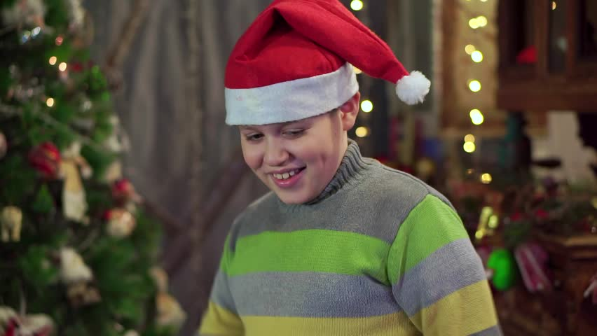 c6cb8d76ec795 A boy teenager in a hat Santa Claus is dancing near the Christmas tree. Christmas  holiday