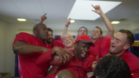 4K Excited American football team celebrate a victory by lifting their coach in the air
