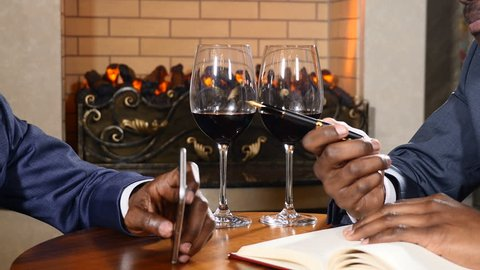Business talks in restaurant with red wine in glasses and a fire place in the background. Close up shot of men hands on table with a notebook. Africo-americans colleagues working together. 4k