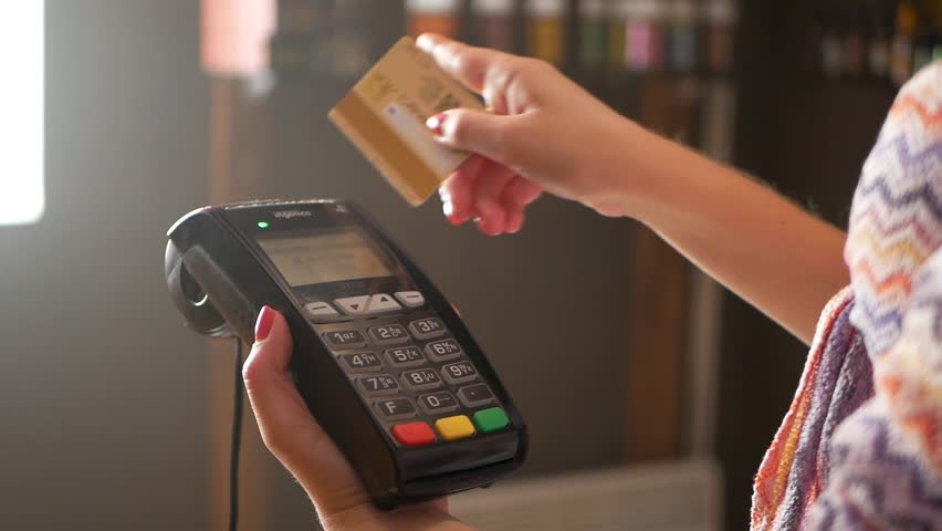 The girl holds in hand a credit card in front of the terminal on white background. A white credit card without image. Payment by a credit card in the terminal