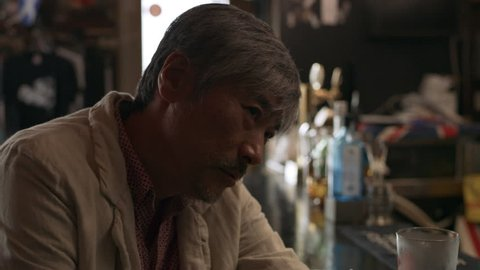 Tired, drunk Japanese man sitting at the bar counter with a cocktail in a dingy bar with soft day lighting. Medium shot on 4k RED camera.
