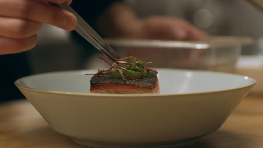 Focused professional chef carefully placing herbs on top of salmon dish in industrial kitchen with soft interior lighting. Close up shot on 4k RED Camera.