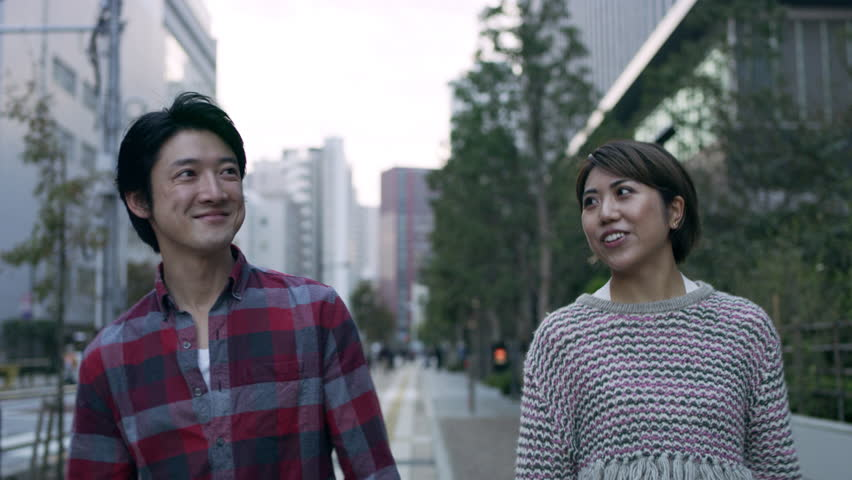 Cheerful happy Japanese couple walking down a quiet metropolitan street with soft natural lighting. Medium shot on 4k RED camera.