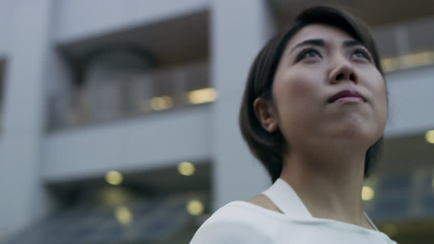 Beautiful Japanese woman looking out while standing in a quiet metropolitan city in Japan with soft natural lighting. Medium close up shot on 4k RED pan around camera on gimbal. | Shutterstock HD Video #1020283150