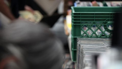 1129. People in a flea market, CD's, vinyls, second hand. Out of focus, people are searching for a CD, a Vinyl, in a second hand store in a flea market in New York City