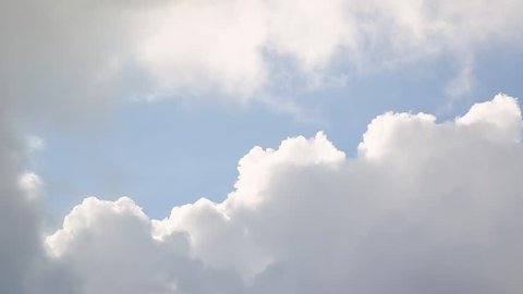 A panning shot of puffy white clouds against a blue sky.