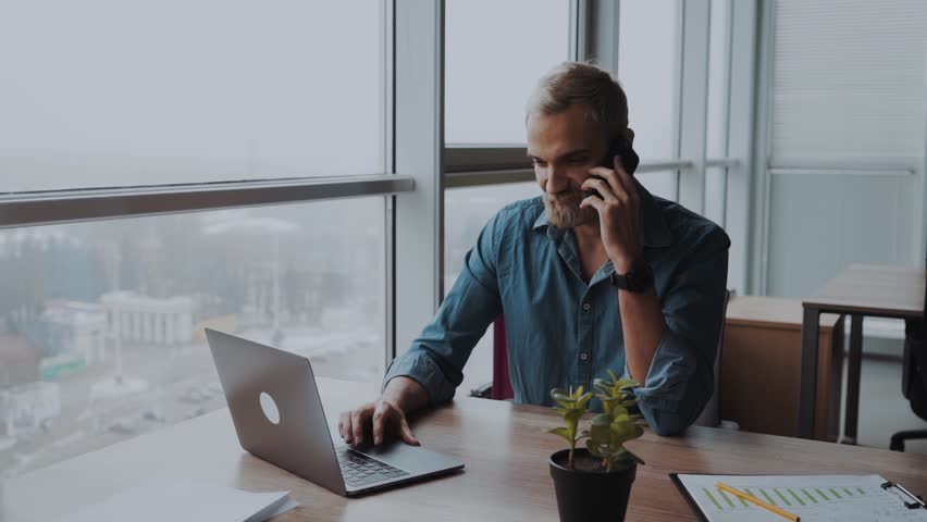 Male businessman is discussing a handheld document on a mobile phone with a pleased smile while seated at his desk in the office working on the computer | Shutterstock HD Video #1020349660