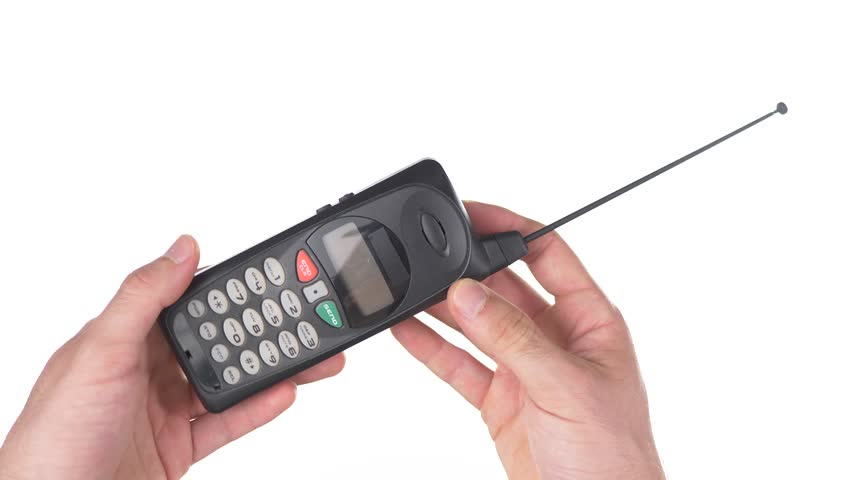 Old vintage cell mobile phone being used against white background