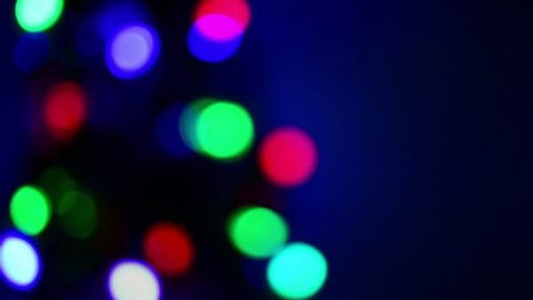 Blurred of Christmas light bokeh decorating on tree blinking in multicolor with black background copy space . Defocused christmas lights,holiday concept.