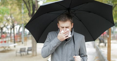 Front view portrait of an ill man walking towards camera sneezing holding an umbrella under the rain