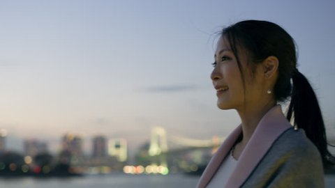 Smiling Japanese woman with ponytail looking out over the water to the skyline of buildings and a bridge with soft natural evening light. Medium shot on 4k RED camera.