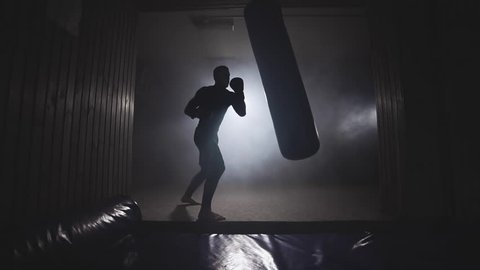 Alone boxer hits punching bag in dark gym. Young man training indoors. Strong athlete in gym. Sport concept. Medium shot. Sportsman boxing in smoky studio