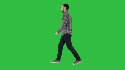 Young casual man walking on a Green Screen, Chroma Key.