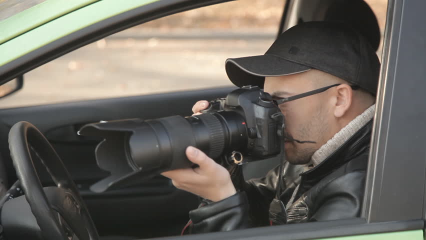 A private detective or a spy conducts surveillance of the object of surveillance. A man secretly taking pictures from the car window | Shutterstock HD Video #1020566710