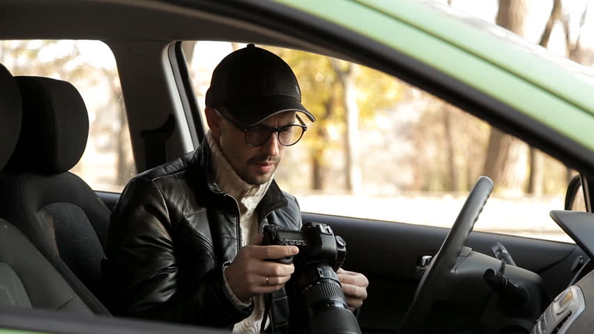 A private detective or a spy conducts surveillance of the object of surveillance. A man secretly taking pictures from the car window | Shutterstock HD Video #1020566740