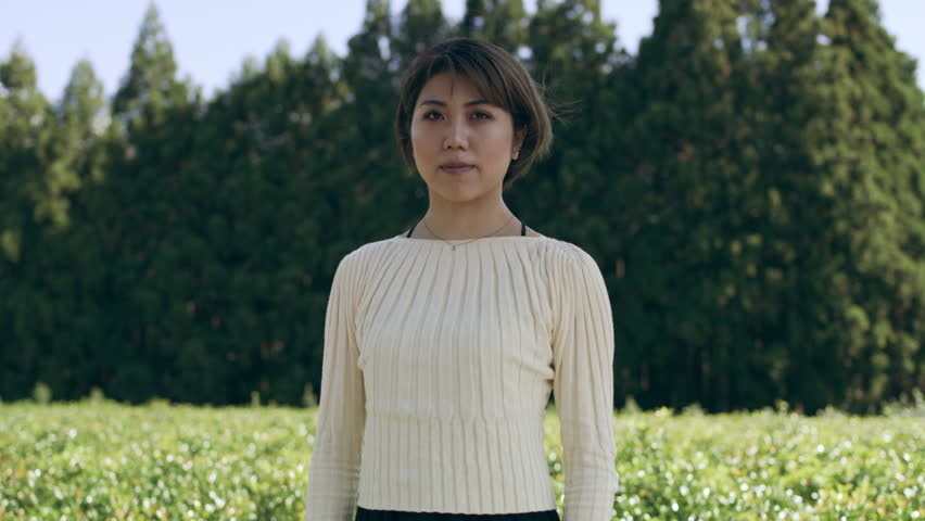 Zoom in Portrait of Japanese woman standing in front of tea plants and trees with soft natural lighting. Medium shot on 4k RED camera.