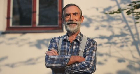 Portrait shot of the senior Caucasian man with grey hair, beard and mustache crossing his hands in front and looking straight to the camera. Outdoors.