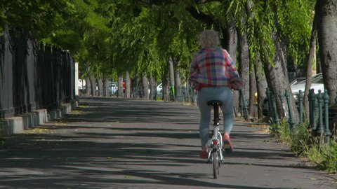 Lockdown: A Bicyclist Leisurely Pedals Away on a Sunny, Tree-Lined Walkway
