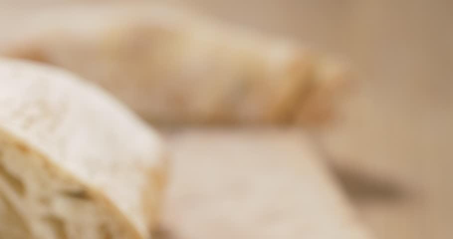 Closeup pan of closeup slices of ciabatta on wood board | Shutterstock HD Video #1020686890