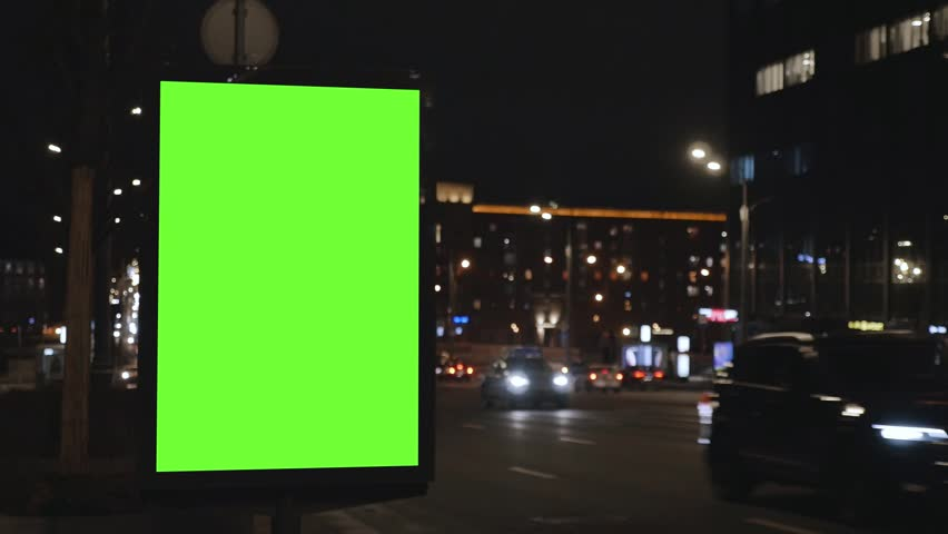 close city light vitrine with empty green screen on roadside against cars driving along night street
