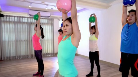 Attractive sporty girl trainer taking teaching lesson to the students wants to burn fats. young ladies and man doing kettlebells exercise at gym. asian people workout in health club.