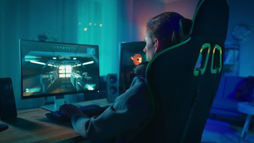 Gamer Puts His Headset with a Mic On and Starts Playing Shooter Online Video Game on His Personal Computer. Room and PC have Colorful Neon Led Lights. Cozy Evening at Home. | Shutterstock HD Video #1020758350
