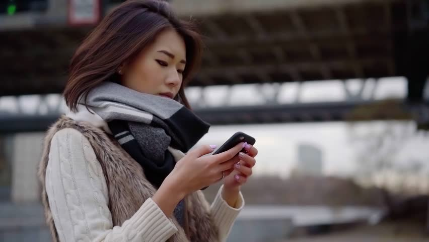 Attractive girl texting on cellphone and get distracted. | Shutterstock HD Video #1020776680