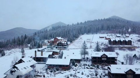 Aerial of inhabited locality in the mountains on winter. Mountain village buildings and houses on snowy hill slopes covered with snow. Countryside, fir tree and pine forest. Cottages of ski resort.