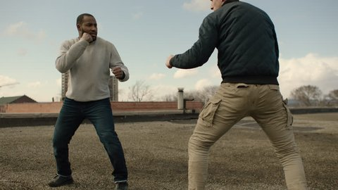 Angry man is knocked to the floor as he fights a bigger man on a warehouse rooftop with skilled kicks and punches in overcast sunlight. Medium shot in 4K with an Alexa Mini camera