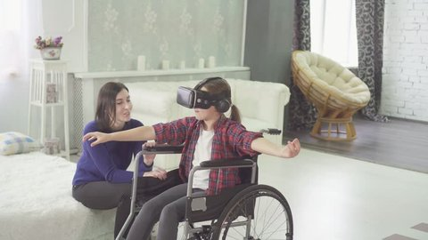 disabled teenager in a wheelchair and her mom at home using vr technology