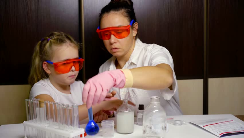Little preschooler girl and her mother are playing like a chemists, mixing liquids in bottle | Shutterstock HD Video #1020857680