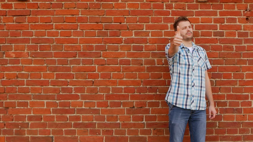 Fashionable and handsome young caucasian man shows like gesture and class against a brick wall, slow motion, copy space   Shutterstock HD Video #1020878230