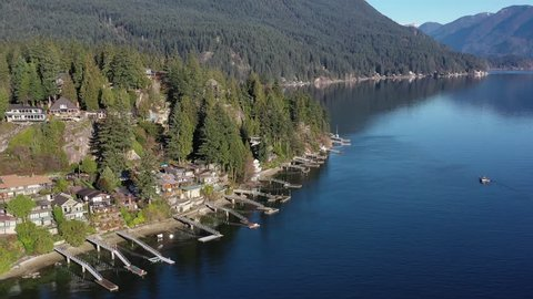 Aerial view over Burrard Inlet, ocean and island with boat and mountains in beautiful British Columbia. Canada.