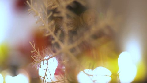 Ornamental snowflake hanging from ceiling in the room, close up, happy new year, best wishes, blinking lights on decorated Christmas tree in blurred background, winter symbol, shallow depth of field.