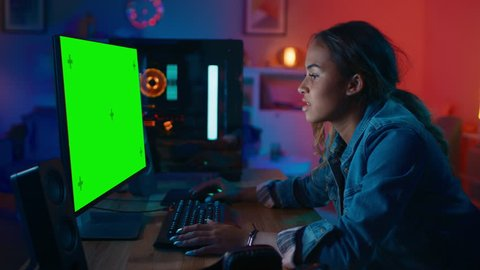 Beautiful Black Girl Freelance Designer Works on a Powerful Gamers Computer with a Green Screen Mock Up at Home. She's Concentrated. Cozy Room is Lit with Warm and Neon Light.