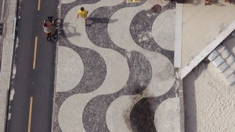 Rio de Janeiro, Brazil, aerial tilt up shot of Copacabana neighbourhood showing people enjoying the summer and walking along the iconic Copacabana Beach mosaic sidewalks.