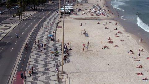 Rio de Janeiro, Brazil, flying over the iconic Copacabana Beach sidewalk, tilt up.