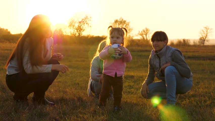 Kid is holding soccer ball in rays of bright sun on field. Happy little girl playing ball with mom and sisters. Family playing with small child by children's ball in park at sunset. Slow motion | Shutterstock HD Video #1020952030