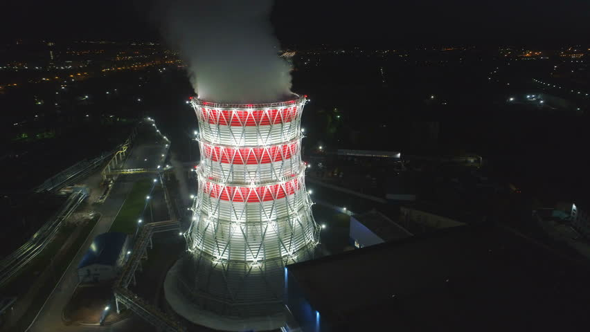 Wonderful aerial motion around brightly lit cooling tower at station and large town in background in early morning | Shutterstock HD Video #1020967960