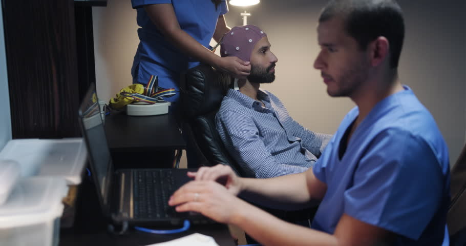 Medical staff performing an EEG on a patient inside the lab of a university clinic. Electroencephalogram test on psychiatric patient performed by doctors. People and professionals in medical industry   Shutterstock HD Video #1020971170
